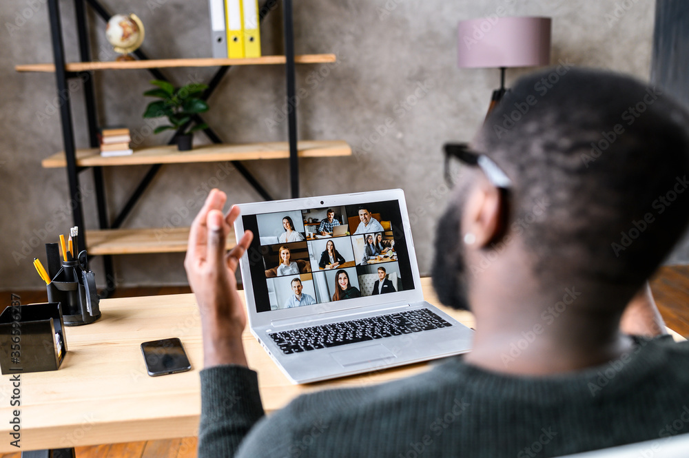 Fototapeta Confident African-American male worker talking online with coworkers, back view of black guy speaks and gestures to many people on video screen. Remote work, virtual meeting
