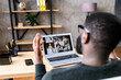 Confident African-American male worker talking online with coworkers, back view of black guy speaks and gestures to many people on video screen. Remote work, virtual meeting