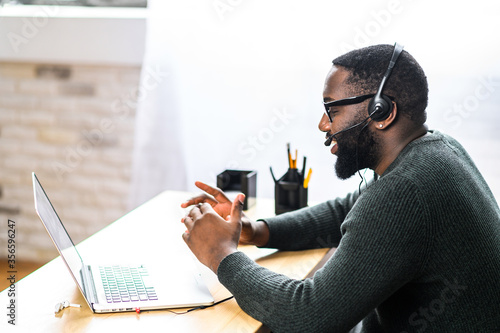 Valokuva Concentrated young guy in smart casual wear and stylish glasses is using headset and laptop for online communication, supporting, selling