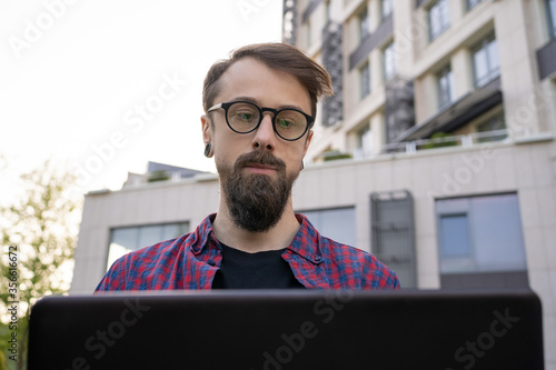 Fototapeta Concentrated bearded man looking at laptop