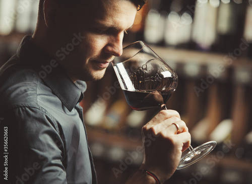 Sommelier smelling flavor of red wine in bokal on background of shelves with bottles in cellar Canvas Print
