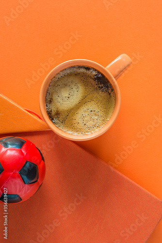 Fotografia, Obraz Orange cup of coffee, football and notebook on orange background with copy spacd