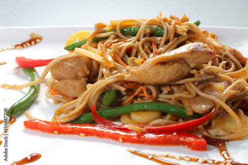 Soy noodles with grilled chicken and vegetables on a white plate Wallpaper Mural
