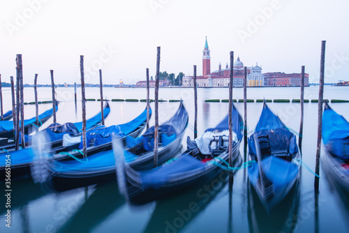 Fototapeta Serene landscape with clear sunrise sky on piazza San Marco in Venice. Row of gondolas parked on city pier. Church of San Giorgio Maggiore on background, Italy, Europe obraz