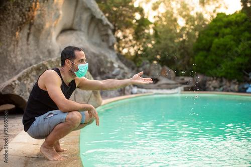 Fotografie, Obraz Uomo moro , con mascherina facciale gioca con l'acqua in piscina