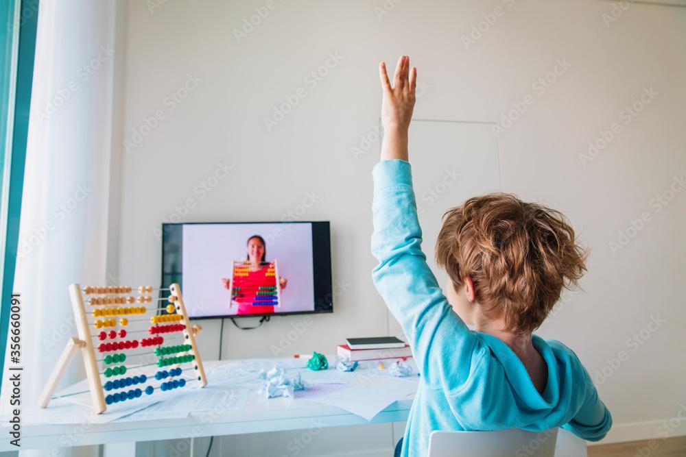 Fototapeta kid learning at home, boy raising hand doing online math lesson