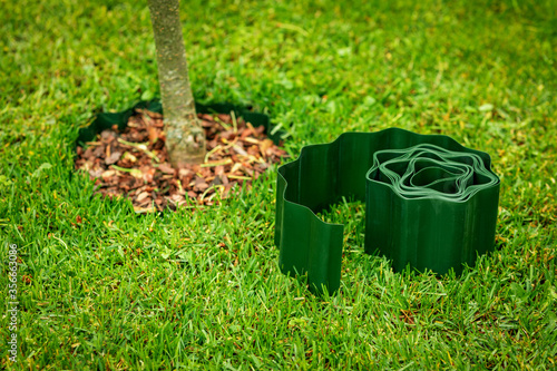 Slika na platnu green plastic lawn edge tape for flowerbed and tree edging
