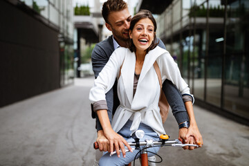 Beautiful happy couple in love on bicycle in the city