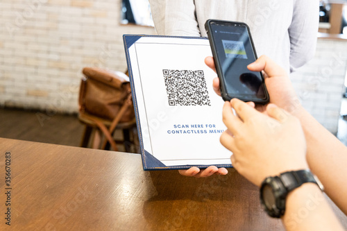 Person scanning contactless menu QR code with smartphone as new normal. Code edited and not valid - 356670283
