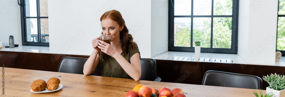 Fototapeta Panoramic shot of woman drinking coffee near croissants on table