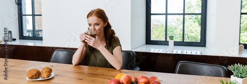 Fototapeta Panoramic shot of woman drinking coffee near croissants on table obraz