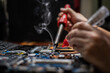 Close-up hand technician repairing broken laptop notebook computer with electric soldering Iron