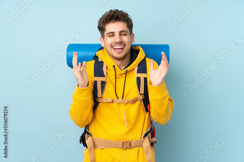 Fotografia Young mountaineer man with a big backpack isolated on blue  background laughing