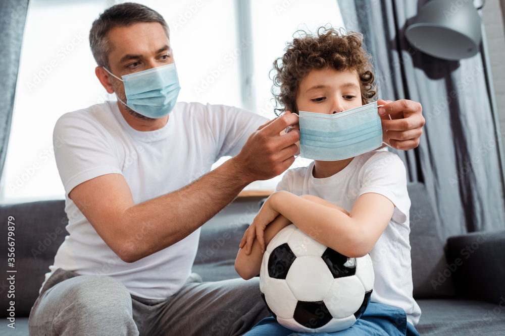 Fototapeta father wearing medical mask on curly son with football