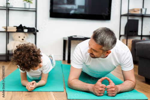 Fototapeta bearded father and curly son exercising on fitness mats obraz