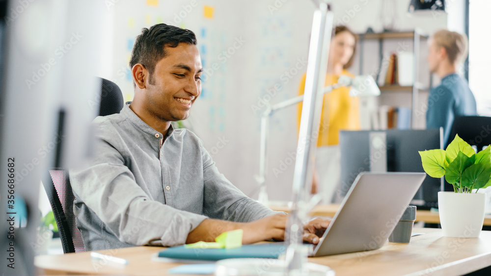 Fototapeta Handsome Smiling Indian Office Worker Sitting at His Desk works on a Laptop. In the Background Modern Office with Diverse Team of Young Professionals Working.
