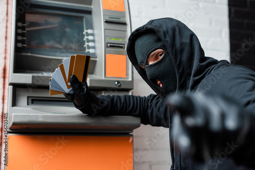 Fotografie, Obraz Selective focus of burglar in balaclava pointing with finger at camera while hol