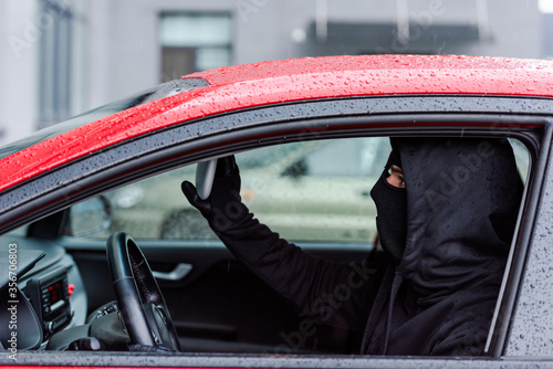 Side view of thief adjusting mirror while sitting in car Canvas Print