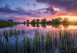 canvas print picture - Beautiful river coast at sunset in summer. Colorful landscape with lake, green trees and grass, blue sky with multicolored clouds and orange sunlight reflected in water. Nature. Vibrant scenery