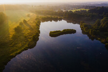 Aerial View Of Osprey Lake Surrounded By Trees At Sunset In Hertford, UK