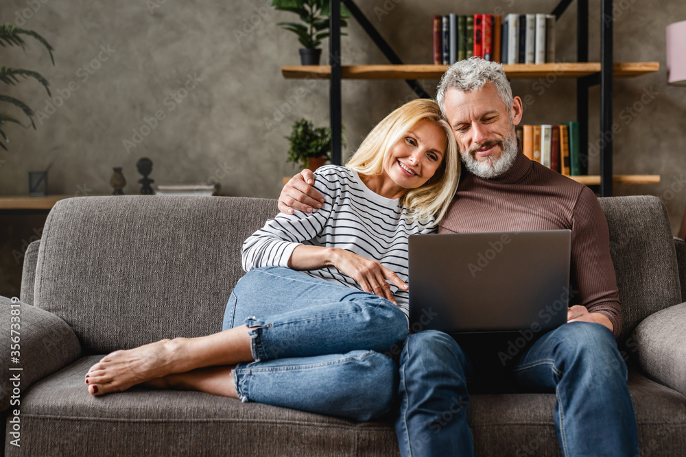 Fototapeta Senior couple using laptop and smiling while resting on couch at homewhile watching movie