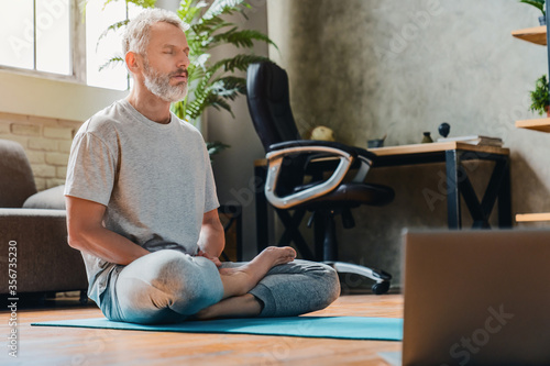 Fotografia, Obraz Middle aged sport man doing yoga and fitness at home using laptop