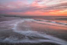 Waves Retreating Back Into The Sea Under A Soft Vibrant Pink And Orange Sky.