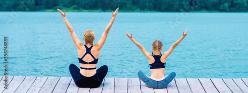 Mother and daughter doing yoga at the shore of the lake in summer Фотошпалери