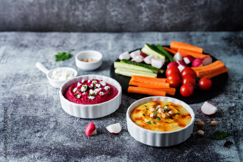Set of classic hummus and beet hummus appetizers with carrot, radish, tomato and Canvas Print