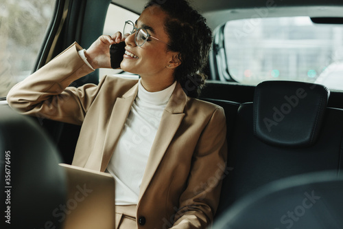 Fototapeta Businesswoman using phone while traveling by a car obraz