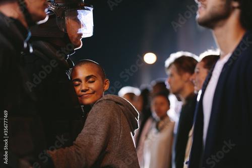 Fototapeta Woman activist hugging a policeman