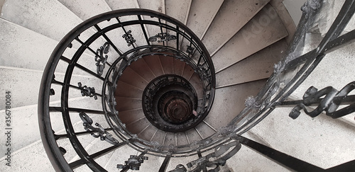 Photo A spiral staircase spiraling down about five floors