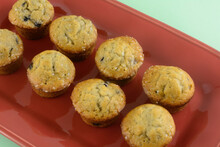 Closeup Of Mini Bite-size Blueberry Muffins On Red Brunch Plate On Green Background