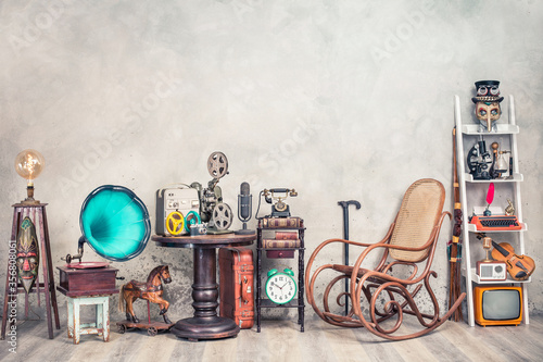 Antique gramophone, rocking chair, old typewriter, retro radio, tape recorder, projector, books, clock, camera, fiddle, mask, cylinder hat, cane, suitcase, bow. Vintage style filtered photo © BrAt82