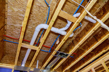 Home Construction With Hot And Cold Blue And Red Pex Pipe Layout In Pipes And Exposed Beams