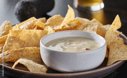 Fototapeta mexican hot queso blanco cheese dip with corn tortilla chips on plate  obraz