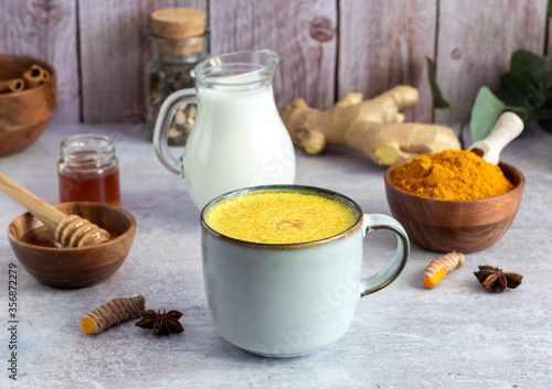 Fototapeta Mug with golden turmeric milk and cinnamon, honey, ginger. Ayurveda treatment. Alternative medicine concept. obraz