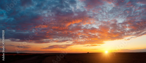 Fototapeta Perfect red clouds illuminated by the beams of the sun. obraz