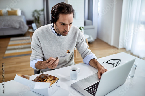 Young businessman using computer while having lunch break at home Fototapete