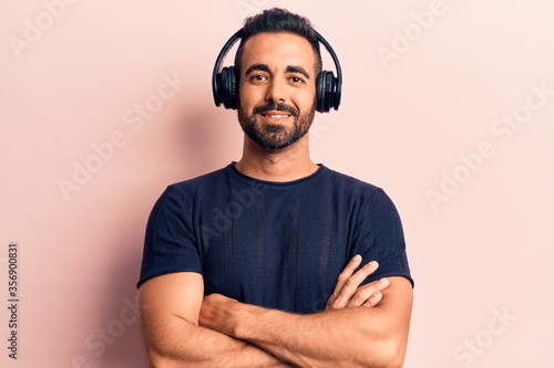Foto Young hispanic man listening to music using headphones happy face smiling with crossed arms looking at the camera