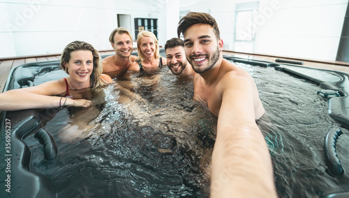 Leinwand Poster Happy friends taking selfie while doing jacuzzi in luxury house - Young people h