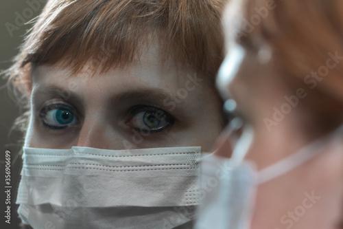 Obraz na plátně Ritratto allo specchio di ragazza con occhi azzurri e mascherina chirurgica