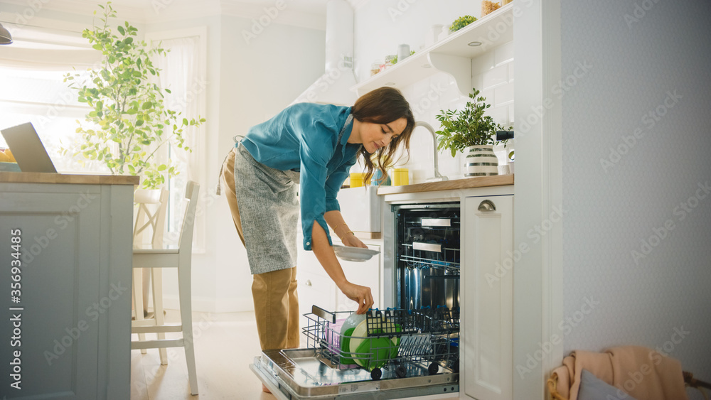 Fototapeta Beautiful Female is Loading Dirty Plates into a Dishwasher Machine in a Bright Sunny Kitchen. Girl in Wearing an Apron. Young Housewife Uses Modern Appliance to Keep the Home Clean.