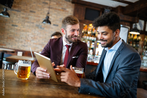 Fototapeta Happy young businessmen in suits are smiling and talking in a restaurant obraz