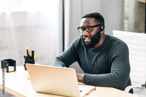 Fotografija Young African-American guy is call center worker or support