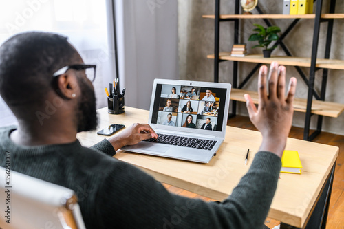Fototapeta Confident African-American male worker talking online with coworkers, back view of black guy is waving hello to many people on video screen. Remote work, virtual meeting obraz
