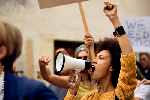 Fototapeta Yung black woman shouting through megaphone on anti-racism demonstrations