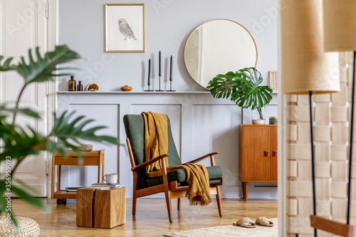 Fototapeta Trendy interior of living room with design armchair, vintage commode, round mirror, mock up poster frame, shelf, tropical leaf, decoration, carpet and persnoal accessories in home decor. obraz