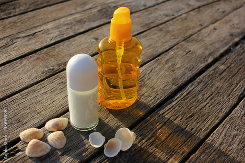 Roll-on antiperspirant deodorant,  sunscreen spray lotion, and seashells on the natural weathered old wooden background with copy space Canvas Print