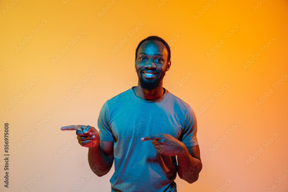 Fototapeta Pointing at side. African-american man's modern portrait on gradient orange studio background in neon light. Beautiful afro model. Concept of human emotions, facial expression, sales, ad. Copyspace.
